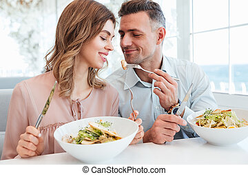 Photo of adult romantic couple having dinner and eating salats while resting in city cafe on sunny day