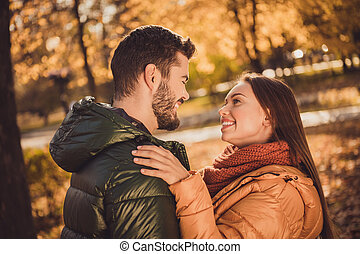 Photo of affectionate trust couple girl look into boyfriends face in fall october forest park wear outerwear coats