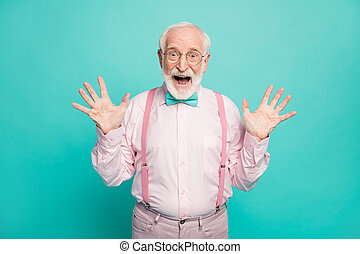 Photo of amazed stylish grandpa positive facial expression smile good mood raise hands wear specs pink shirt suspenders bow tie pants isolated bright teal color background