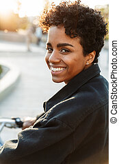 Photo of amazing african american woman looking at camera while sitting on bicycle in city park