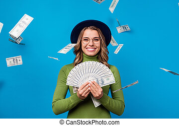 Photo of amazing cheerful lady hold fan dollar bucks rich freelance salary success business woman money falling from sky wear specs hat green turtleneck isolated blue color background