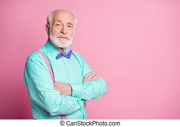 Photo of amazing stylish look grandpa hands crossed seriously facial expression wear mint shirt suspenders violet bow tie isolated bright pink color background