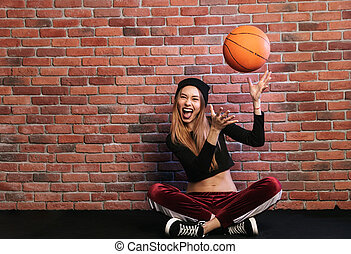 Photo of artistic girl 20s, sitting on floor against brick wall and playing with basketball