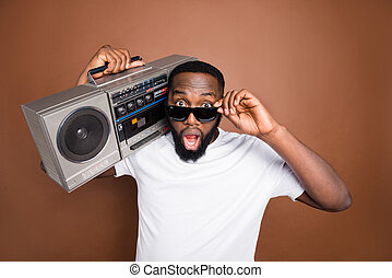 Photo of astonished casual man holding retro audio recorder wearing white t-shirt and eyewear sunglass isolated over pastel color brown background listening to music