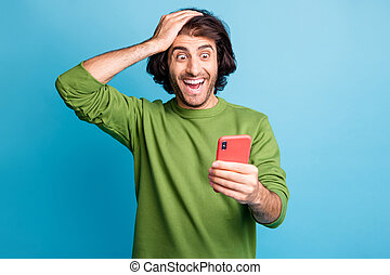 Photo of astonished person open mouth arm on head look screen wear pullover isolated on blue color background