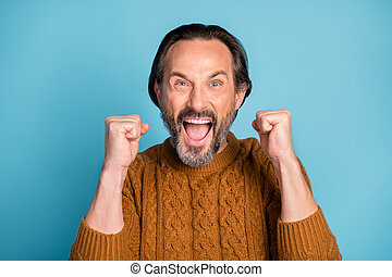 Photo of astonished person open mouth scream yeah fists up celebrate isolated on blue color background