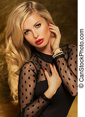 Portrait of elegant blonde beauty looking at camera. Beautiful woman posing with red lips and curly long hair.