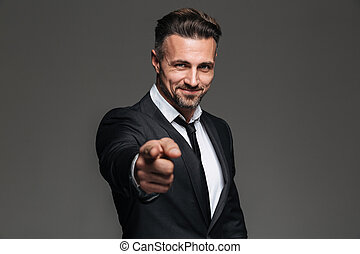 Photo of attractive businessman in suit smiling and pointing index finger on camera, isolated over dark gray background