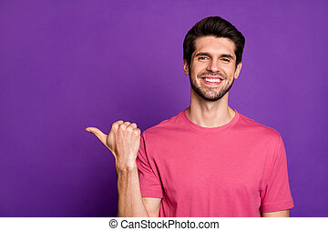 Photo of attractive handsome guy good mood direct thumb finger side empty space show cool offer low shopping price wear casual pink t-shirt isolated purple color background
