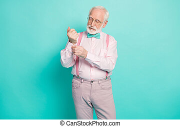 Photo of attractive hipster grandpa preparing senior meeting party buttoning sleeve carefully wear specs pink shirt suspenders bow tie pants isolated teal color background