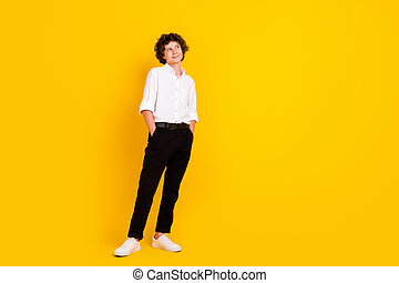 Photo of attractive pretty school boy wear white shirt smiling arms pockets looking empty space isolated yellow color background