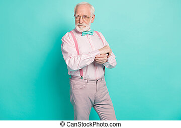 Photo of attractive serious grandpa prepare senior meeting party buttoning sleeve look side empty space wear specs pink shirt suspenders bow tie pants isolated teal color background