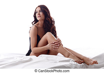 Photo of attractive young brunette sitting in bed