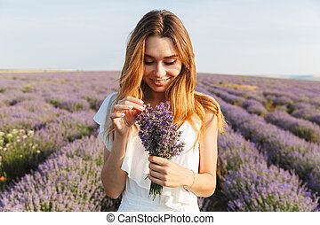 Photo of attractive young woman in dress holding bouquet of flowers, while walking outdoor through lavender field in summer