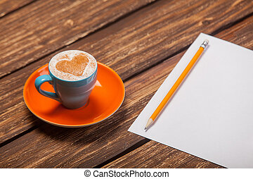 photo of beautiful blue cup of coffee and sheet of paper with pencil on the wonderful brown wooden background