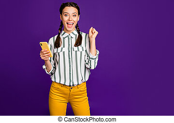 Photo of beautiful crazy lady holding telephone reading post positive good comments and likes celebrating wear striped shirt yellow trousers isolated purple color background
