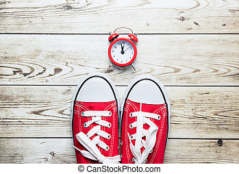 photo of beautiful red gumshoes and alarm clock on the wonderful white wooden studio background