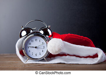 photo of beautiful Santa Claus hat and cool alarm clock on the wonderful grey studio background