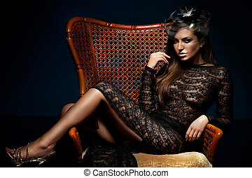 Photo of beautiful sexy brunette woman posing, sitting on chair, wearing black elegant dress. Looking at camera.