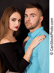 Beautiful young stylish man and woman on a black background
