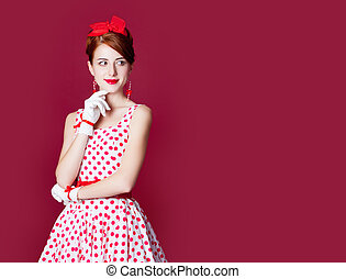 photo of beautiful young woman in vintage dotted dress on the wonderful burgundy background