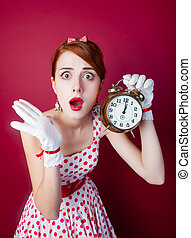 photo of beautiful young woman in vintage dotted dress with alarm clock on the wonderful burgundy background
