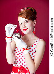 photo of beautiful young woman in vintage dotted dress with cake on the wonderful burgundy background