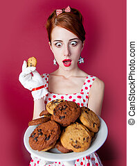 photo of beautiful young woman in vintage dotted dress with cookies on the wonderful burgundy background