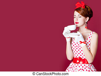 photo of beautiful young woman in vintage dotted dress with cup of coffee on the wonderful burgundy background
