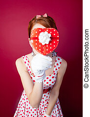 photo of beautiful young woman in vintage dotted dress with cute box on the wonderful burgundy background