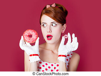 photo of beautiful young woman in vintage dotted dress with donut on the wonderful burgundy background