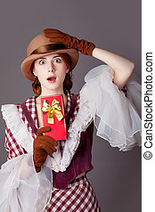 photo of beautiful young woman in vintage dress with cute gift on grey background