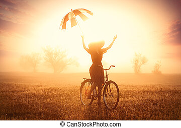 photo of beautiful young woman on bicycle with umbrella on the wonderful sunset background