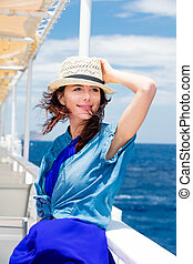 photo of beautiful young woman on the boat in front of sea background in Greece