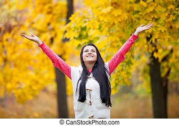 photo of beautiful young woman on the wonderful yellow trees background