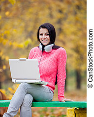 photo of beautiful young woman sitting on the bench in headphones with laptop on the wonderful yellow trees background