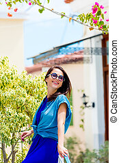 photo of beautiful young woman standing near tree and house in Greece