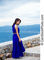 photo of beautiful young woman standing on the stairs in Greece