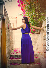 photo of beautiful young woman standing on the stairs near blooming tree in Greece