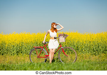 photo of beautiful young woman with bicycle on the wonderful flower field background