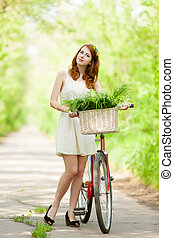photo of beautiful young woman with bicycle on the wonderful park background