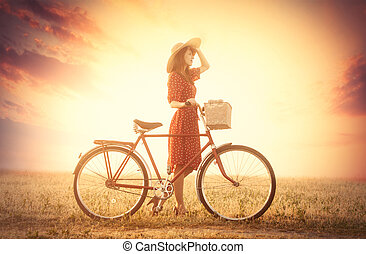 photo of beautiful young woman with bicycle on the wonderful sunset background