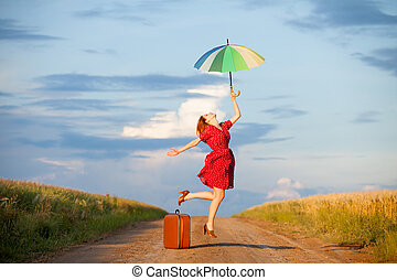 photo of beautiful young woman with suitcase and umbrella on...