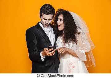Photo of beautiful zombie couple bridegroom and bride wearing wedding outfit and halloween makeup using smartphone, isolated over yellow background
