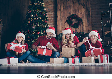 Photo of big family wondered dad mom sister brother opening x-mas gifts sitting floor near decorated garland lights newyear tree indoors wear santa caps red pullovers