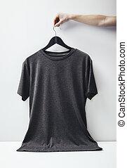 Photo of black tshirt holding on white background