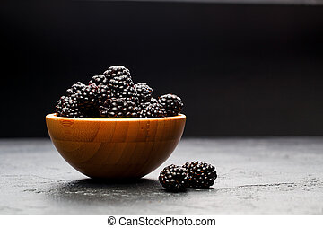 Photo of blackberry in wooden cup on empty black background.