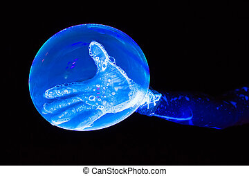 Photo of blue luminous glove and bubble on black background