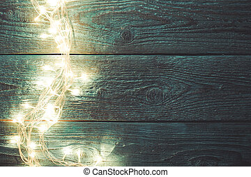 Photo of blue wooden table with burning garland on side