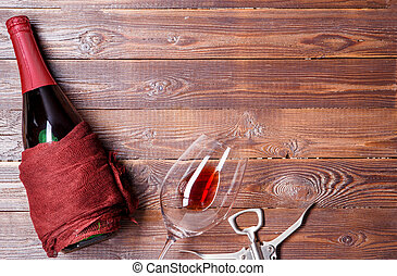Photo of bottle of wine, corkscrew, wine glass on brown